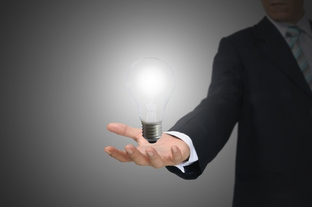 Light bulb in hand business man on grey background