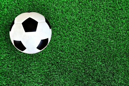 Football or soccer ball on artificial grass field photo