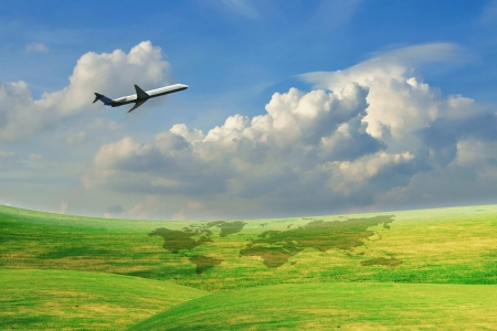 Airplane flying over green field with blue sky Stock Photo