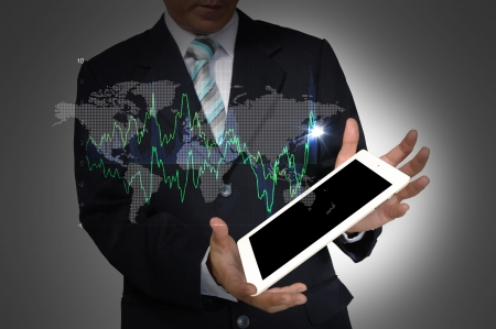 Business Man present world graph with tablet PC photo