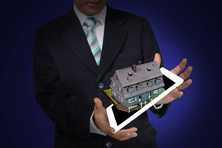 Business Man present house on tablet PC photo