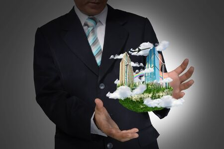 Business Man holding floating city on grey background photo