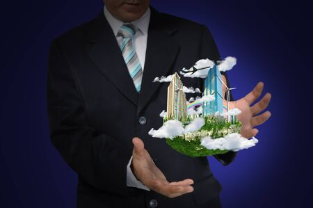 Business Man holding floating city on blue background photo