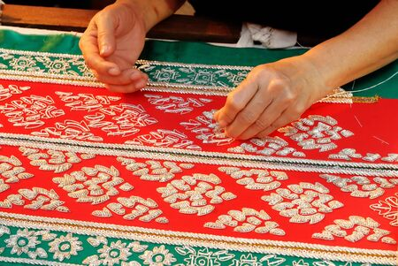 Female Hand stitching cloth to make ancient Thai pattern fabric  photo