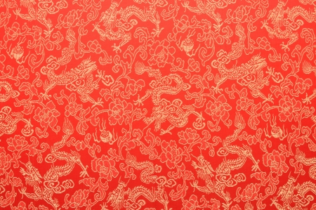 Fragment of red chinese silk with golden dragons and flowers Standard-Bild