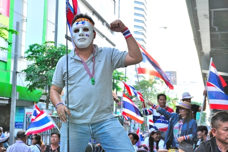 BANGKOK-JANUARY 13: Unidentified protestor wearing white mask  in anti-government group on RAMA 4 street on Jan 13, 2014 in Bangkok, Thailand.