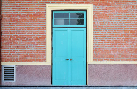 blue wooden door and brick wall photo