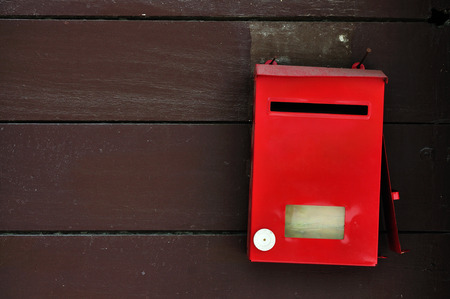 postoffice: Red postbox on brown wood wall