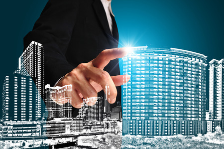 architect drawing: Business man or achitect touch the drawing of building or cityscape