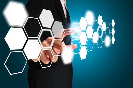 gray suit: Business man touching an imaginary screen on blue background Stock Photo