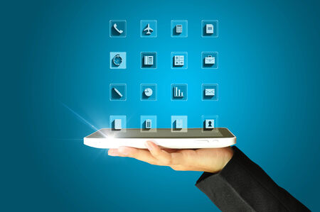 Woman hands holding tablet PC with application icons on blue background photo