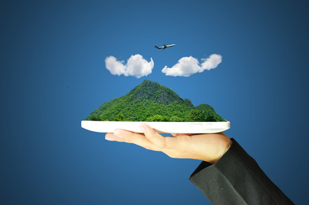 Hand holding touch screen tablet present green mountain, cloud and airplane  photo