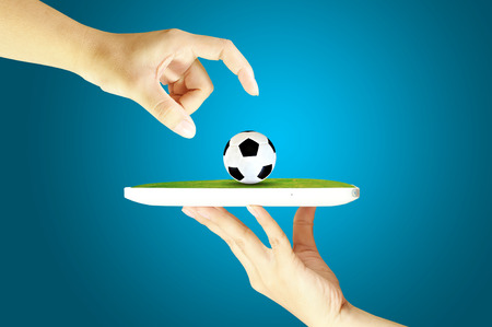 Hand give and take soccer or football bal over mobile device  photo