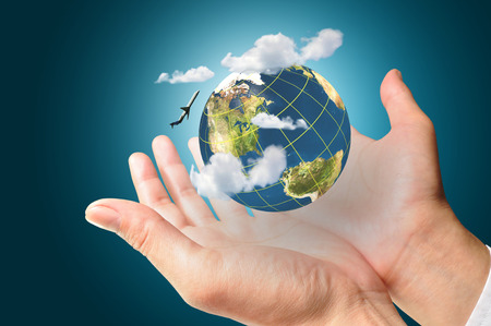 Businessman holds Earth in a hand with airplane and cloud present air transportation concept.   photo