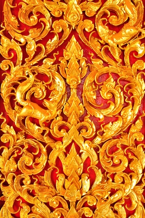 Thai Art of Gold wood Carving on red background photo