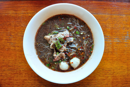 Rice Vermicelli noodle in Thicken soup with Porkball and Sliced pork.  It is called Kuay Teow Reua Stock Photo