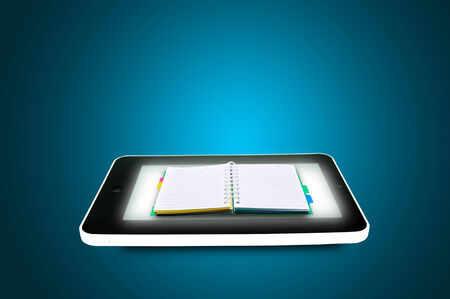 Black tablet pc with book or Diary on blue background. Portable computer notebook or Diary concept  photo