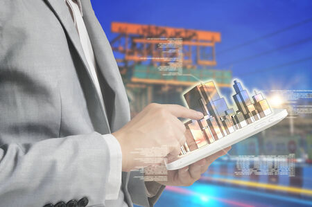 Young Business man using Tablet PC to present the Building as Building business concept photo