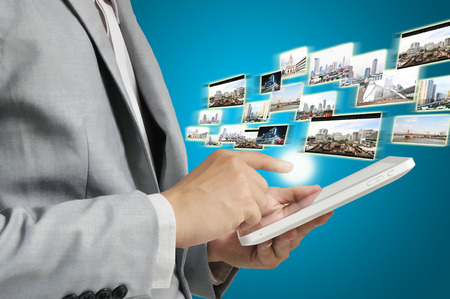 Business Man Holding Tablet sending or receiving Streaming images via wireless communication photo
