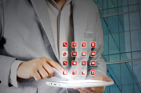 Business man touch tablet display to access the software application as wireless device concept photo