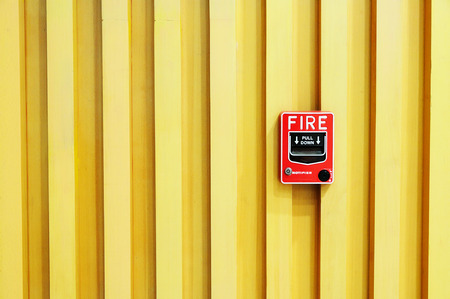 Fire alarm red box warning machine on wooden background. photo