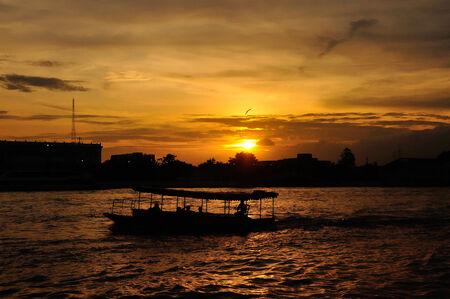 praya: Silhouette of the boat at sunset at Chao Praya river. Bangkok, Thailand.  Stock Photo