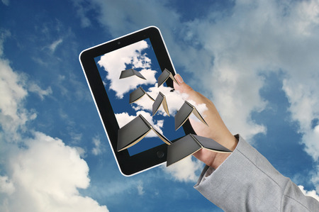 Business Man Hand hold Touch screen Tablet receive Flying Book as Cloud computing concept photo