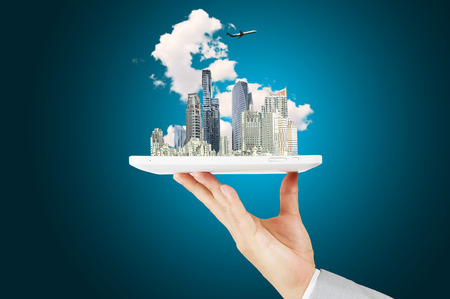 Male Hand Hold tablet with Moderncity Building, Cloud and Airplane photo
