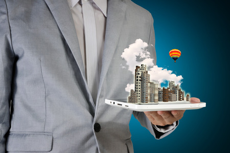 Business Man hold Tablet with 3d Modern City and Balloon photo