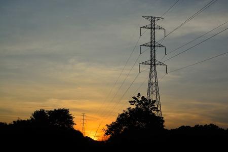 torres el�ctricas: Potencia poste. Torres de energ�a en el sol poniente de la oscuridad