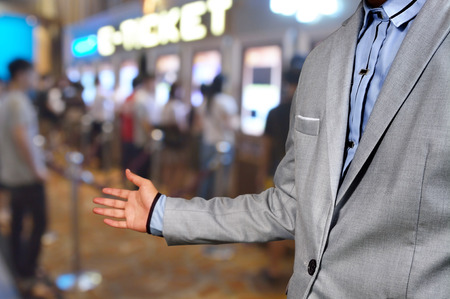 Business Man show welcome or invite gesture on Movie Ticket System Background as Entertainment business or Theatre cinema complex concept. Stock Photo