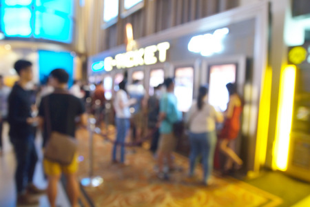 Blur or Defocus image of People line up to buy Movie Ticket from e-ticket or E-machine system.