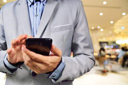 Business Man Touch his Mobile Phone in Modern Building Environment Background photo