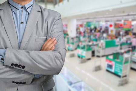 distribution: Business Man stand in Hypermarket or Supermarket store present retail marketing Stock Photo