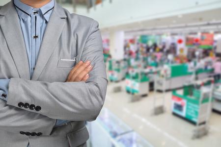 gerente: El hombre de negocios de pie en el hipermercado o supermercado presente comercialización al por menor