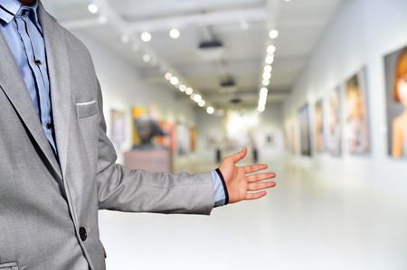 Artist or Photographer or Manager welcome guest to his image exhibition show in art gallery