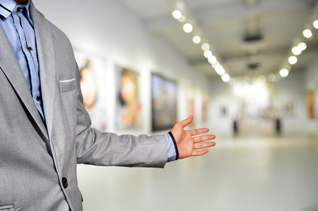 business exhibition: Artist or Photographer or Manager welcome guest to his image exhibition show in art gallery
