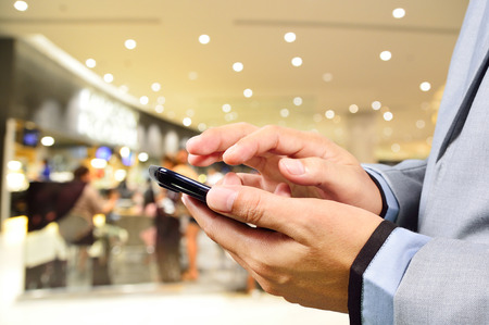 Handsome young man in shopping mall using mobile phone photo