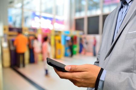 Business Man met behulp van digitale mobiele telefoon met achtergrond van mensen met behulp van ATM als Mobile Banking Concept.