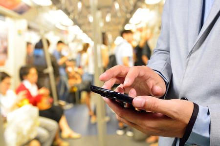 black train: Business Man using Mobile Phone in Train or Subway Stock Photo