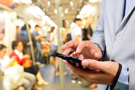 hablando por telefono: Hombre de negocios que usa el tel�fono m�vil en tren o metro