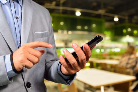 food restaurant: Business man using mobile smart phone in Restaurant or Food Court Plaza Stock Photo