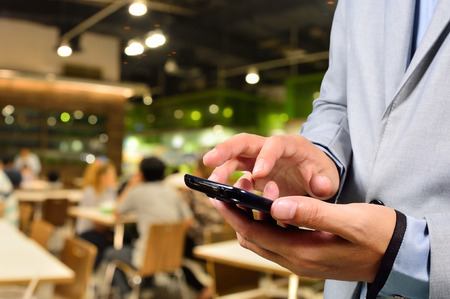 food court: Business man using mobile smart phone in Restaurant or Food Court Plaza Stock Photo