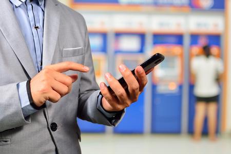 cuenta bancaria: Businesssman usando móvil aplicación de banca en Smartphone cerca de cajero automático o sistema de cajeros automáticos como Tele-banca o de compra en línea concepto