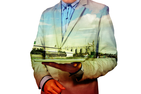 Double Exposure of Businessman and Silo warehouse and Blue sky as Agricultural Business Technology concept.