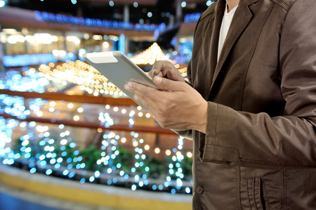 finger on trigger: Young Man Hands holding Tablet or Mobile Device in Shopping Mall at Night.  Selective Focus on Right Pointer Finger or Trigger Finger.