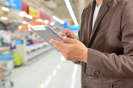 Young Man Hands holding Tablet or Mobile Device in Supermarket or Hypermarket store as Digital environment Working. Selective Focus on Right Pointer Finger or Trigger Finger.