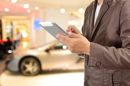 finger on trigger: Young BusinessMan using Tablet device with Modern Sportcar as Modern Lifestyle Concept.  Selective Focus on Right hand Trigger finger .
