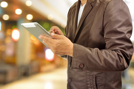 finger on trigger: Young Man Hands holding Tablet in Shopping Mall or Department Store. Selective Focus on Right Pointer Finger or Trigger Finger. Stock Photo