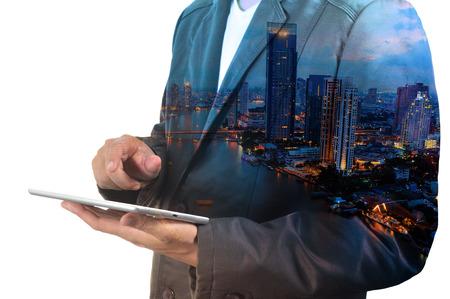 都市およびビジネスマンの二重露光は、ビジネス開発コンセプトとしてタブレット デバイスを使用します。